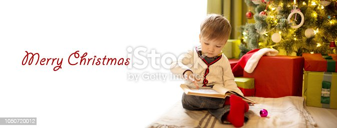 istock Cute little boy reading a book in front of the christmas tree at home with copy space for text 1050720012