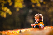 Cute little boy relaxing in autumn leaves at the park.