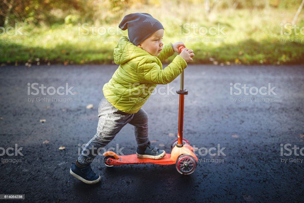 Cute little boy rides on a kick scooter – Foto