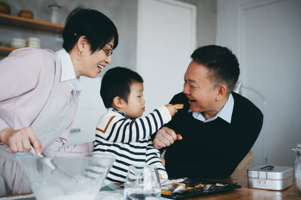 cute little boy sharing cookies with grandfather while preparing food with grandparents together in the kitchen - baking bread at home imagens e fotografias de stock