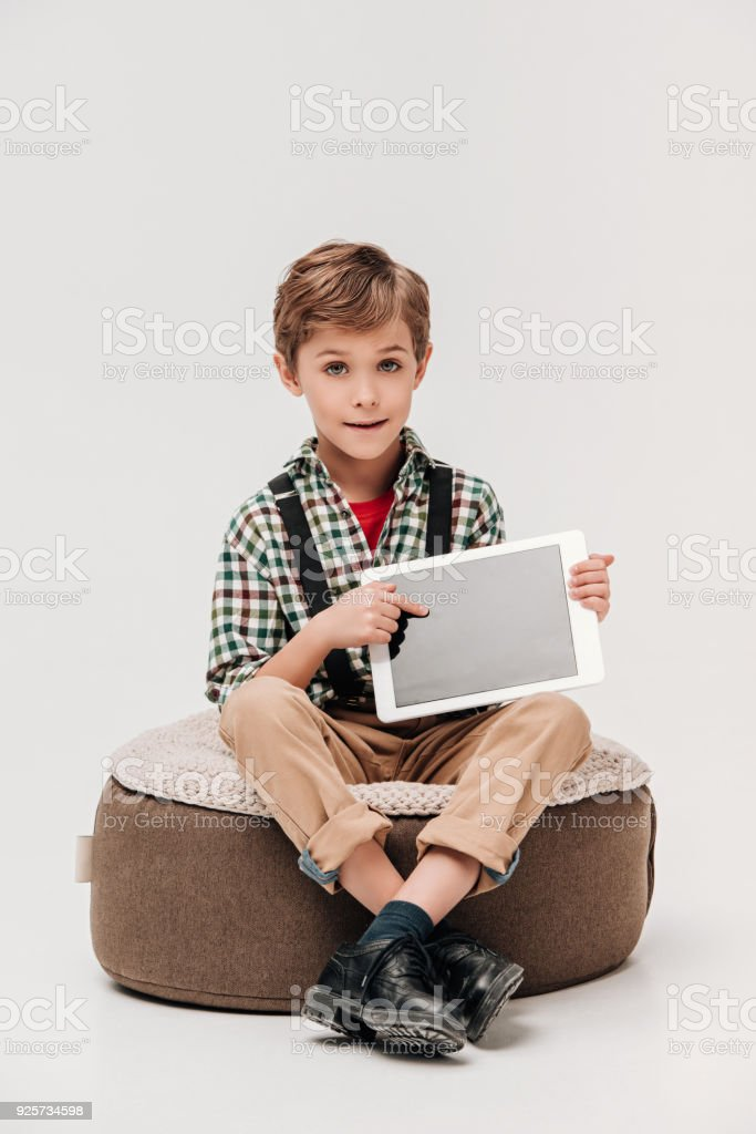 cute little boy showing digital tablet with blank screen and looking at camera isolated on grey stock photo