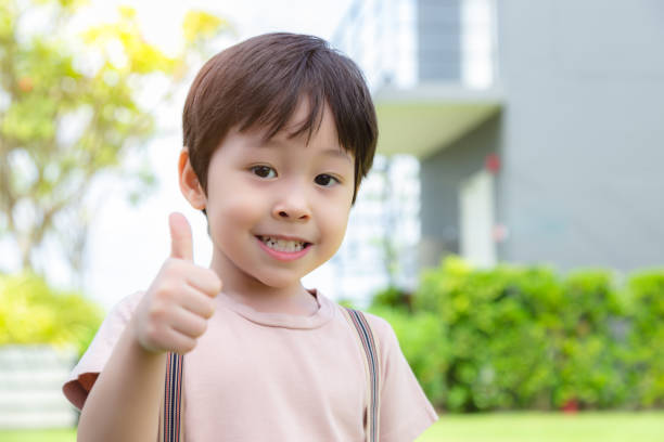 Cute little boy showing thumb up with smiley face. Lovely boy feel happy and relaxed. He has good health and enjoy life. Little child is preschool boy. Handsome boy look clever and smart. copy space stock photo