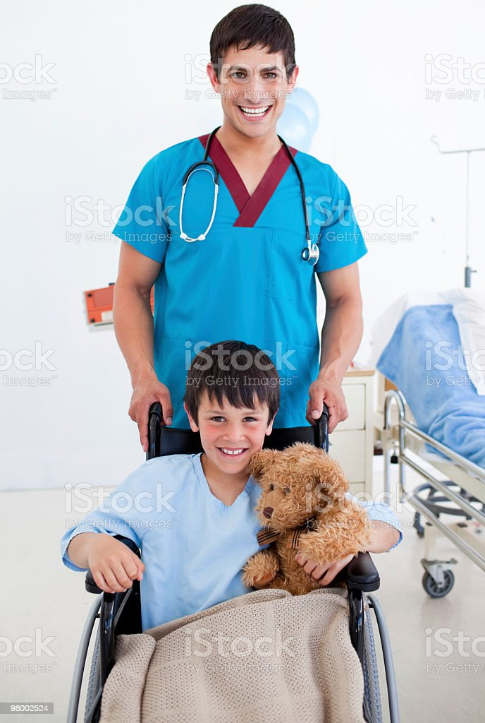 Cute little boy sitting in a wheelchair with his doctor royalty-free stock photo