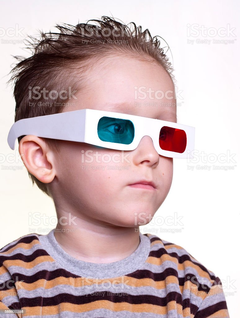 cute little boy sitting in the 3D glasses stock photo