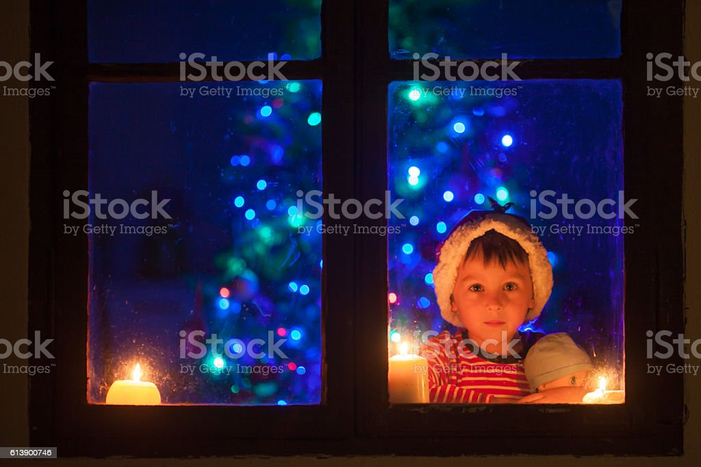 Cute little boy, sitting on a window at night stock photo