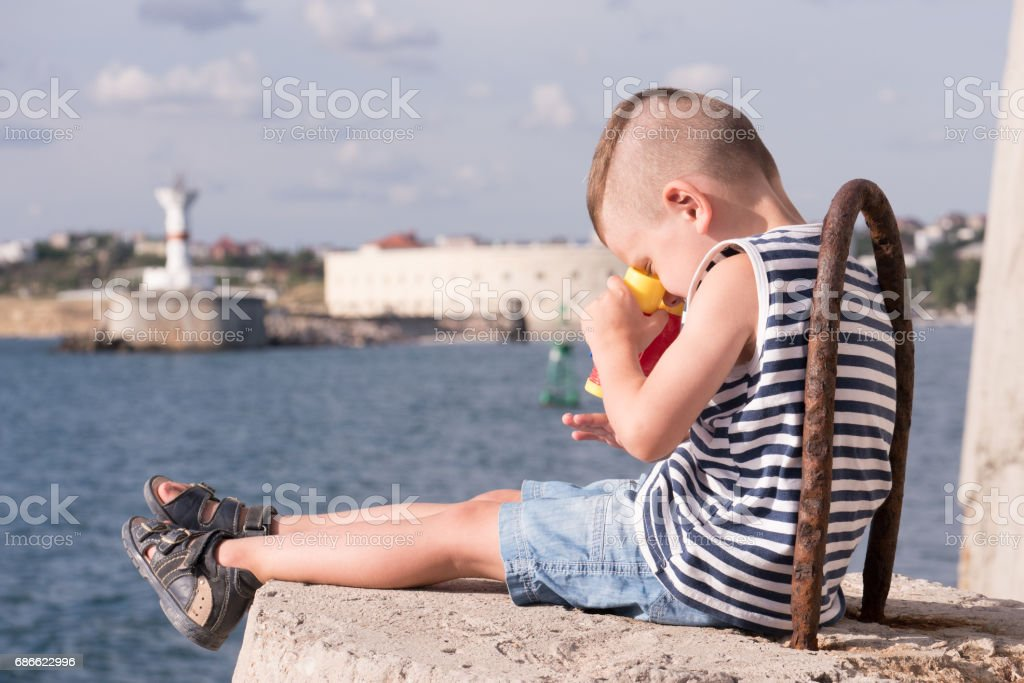 cute little boy sitting on breakwater on background of sea and looking through binoculars down on his hand royalty-free stock photo
