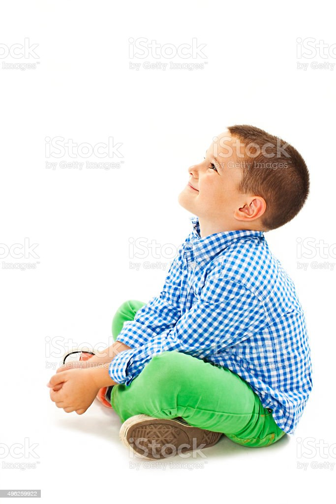 Cute little boy sitting on the floor, looking up stock photo