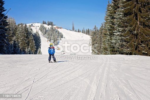 istock Cute little boy, skiing happily in Austrian ski resort in the mountains 1194719325