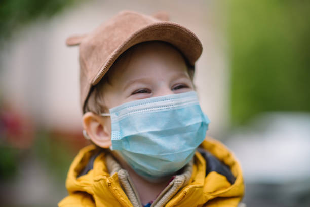 Cute little boy smiling behind protective mask outdoors