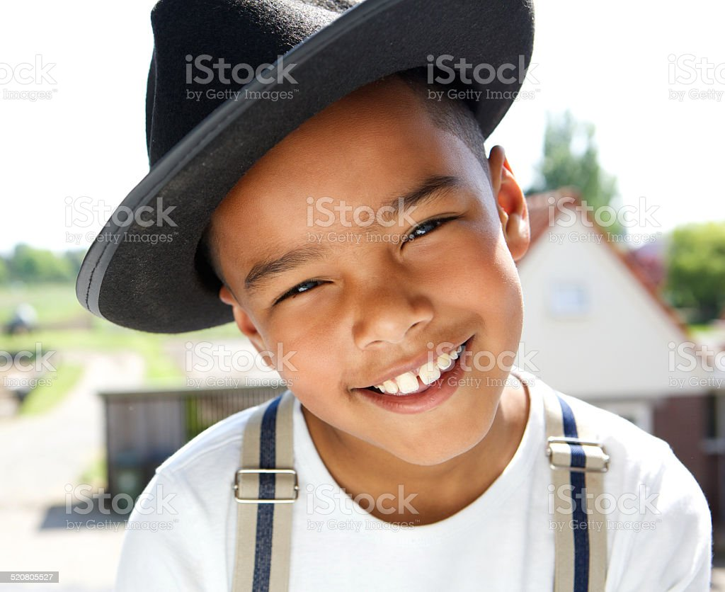 Cute little boy smiling with hat outdoors stock photo