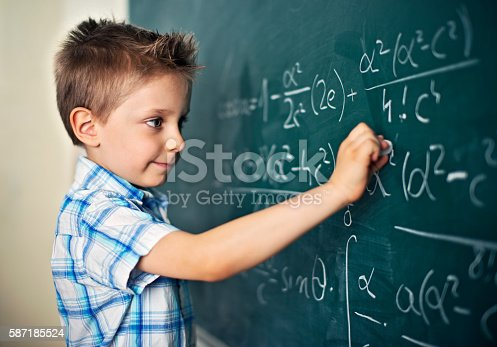 istock Cute little boy solving difficult mathematical problems 587185524