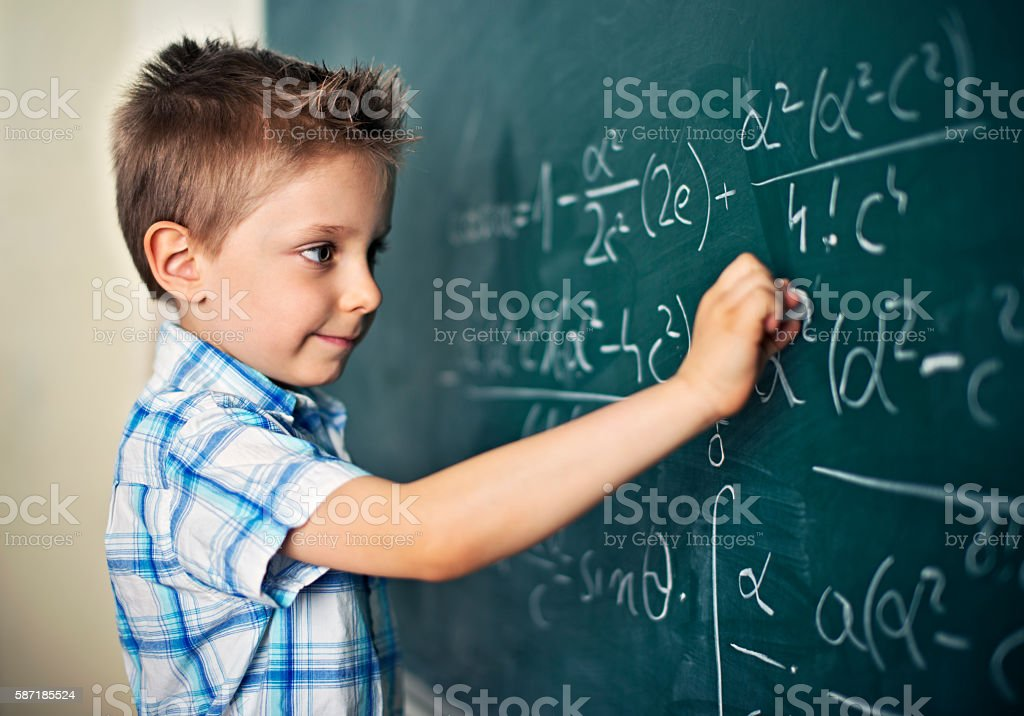 Cute little boy solving difficult mathematical problems stock photo