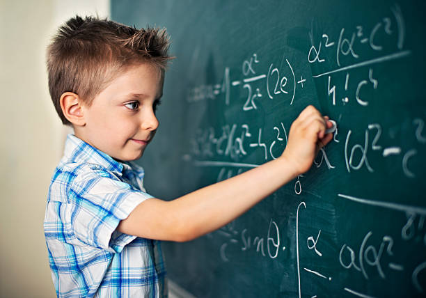 Cute little boy solving difficult mathematical problems – Foto