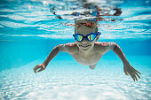 Portrait of smiling little boy swimming underwater in the pool towards the camera. Sunny summer day.\nNikon D850