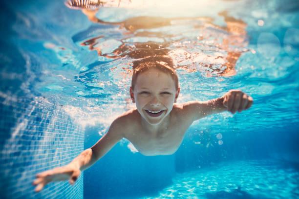 Niedlichen kleinen Jungen schwimmen unter Wasser im pool – Foto