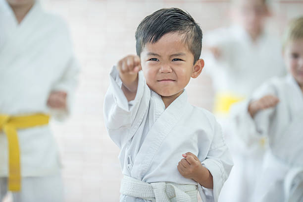 cute little boy taking karate - artes marciales fotografías e imágenes de stock