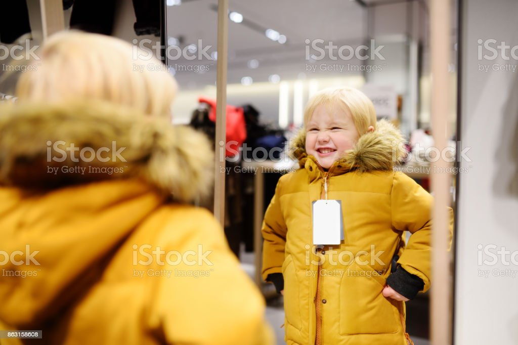 Cute little boy trying new coat during shopping stock photo