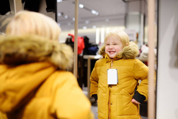 Cute little boy trying new coat during shopping - foto stock