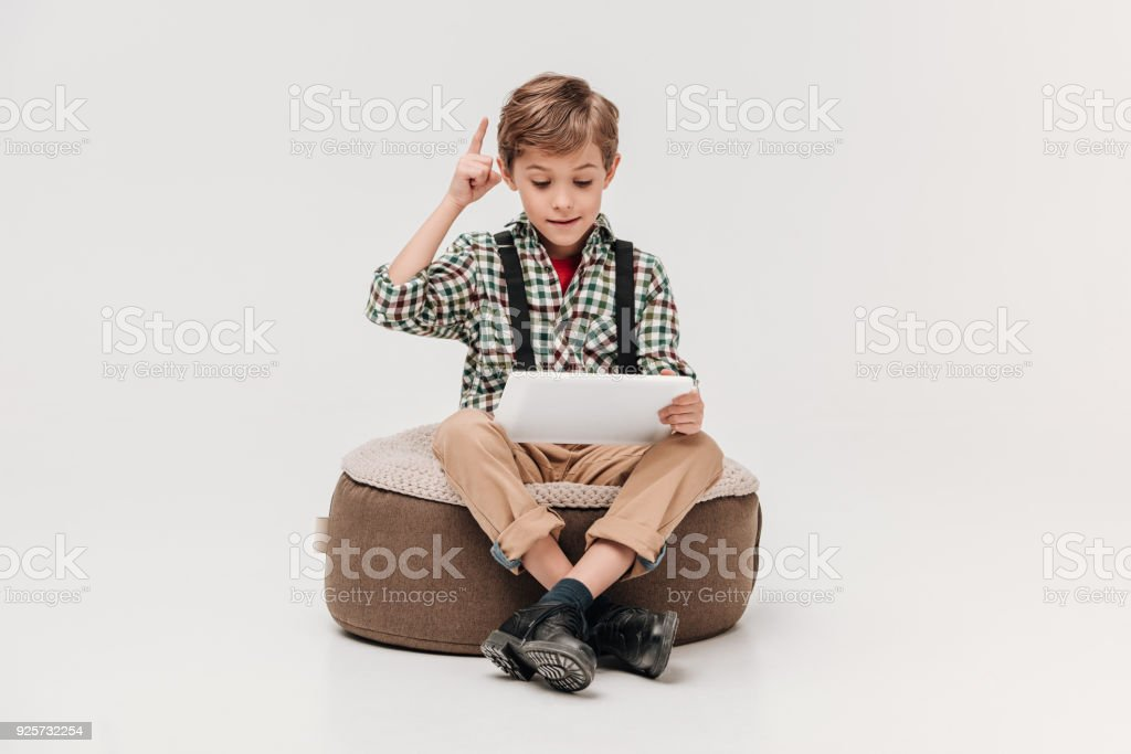 cute little boy using digital tablet and pointing up with finger isolated on grey stock photo