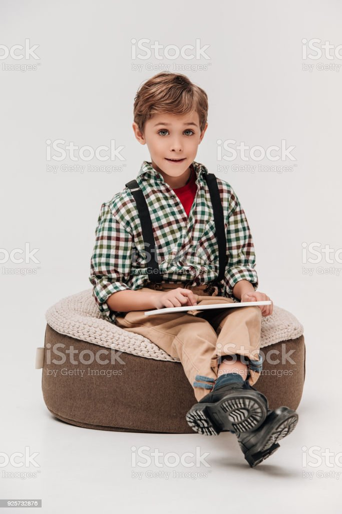 cute little boy using digital tablet and smiling at camera isolated on grey stock photo
