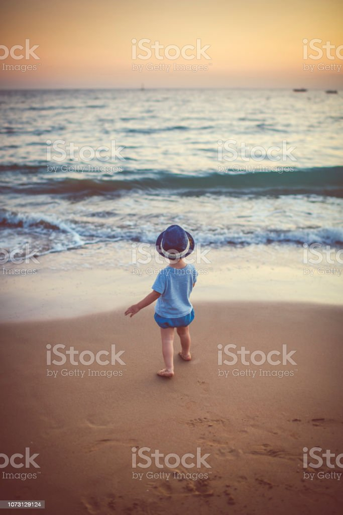 Cute little boy walking on the beach in sunset stock photo