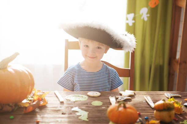 niedliche kleine junge tragen piratenkostüm an halloween süßes oder saures. kinder schnitzen kürbis laterne. kinder feiern halloween im inneren des wohnzimmer dekoriert für halloween-party im hintergrund - piratenzimmer themen stock-fotos und bilder