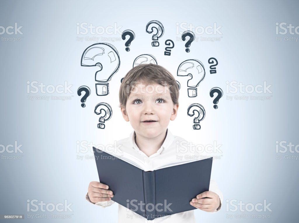 Cute little boy with a book, question marks stock photo