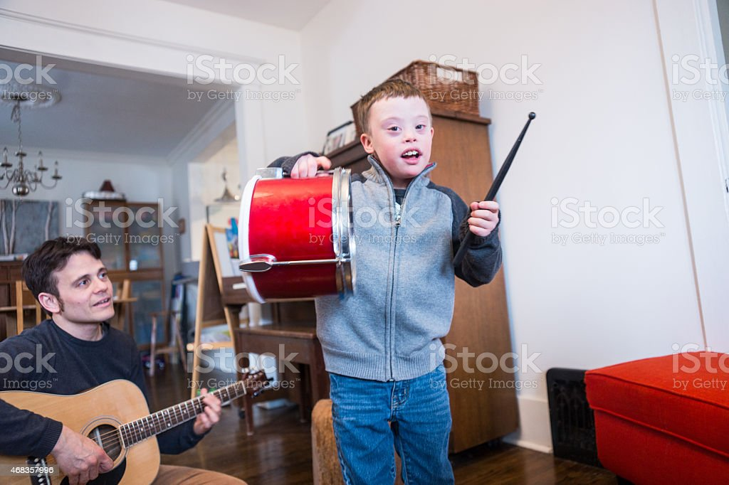 Cute little boy with Downs Syndrome playing music royalty-free stock photo