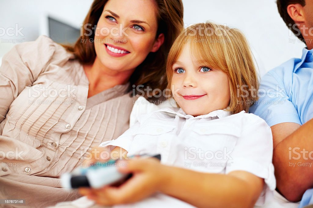 Cute little boy with his parents watching television royalty-free stock photo