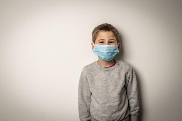 Netter kleiner Junge mit medizinischer Maske im Gesicht – Foto