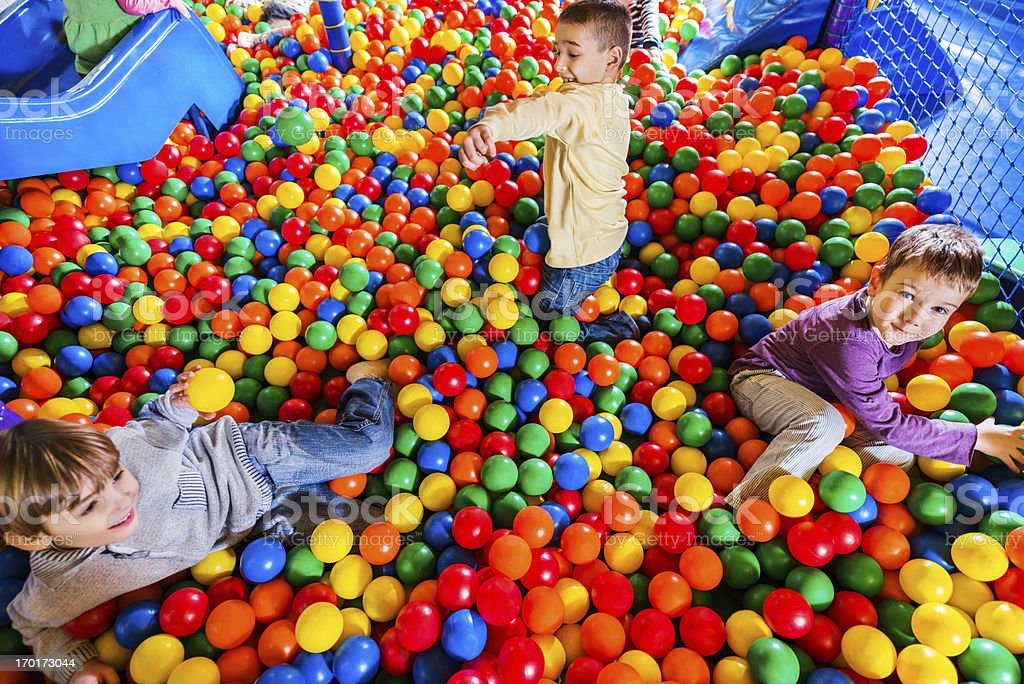 Cute little boys playing in the ball pool. stock photo