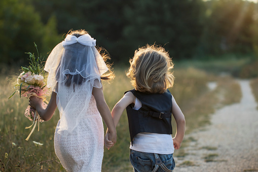 Cute little bride and groom running together