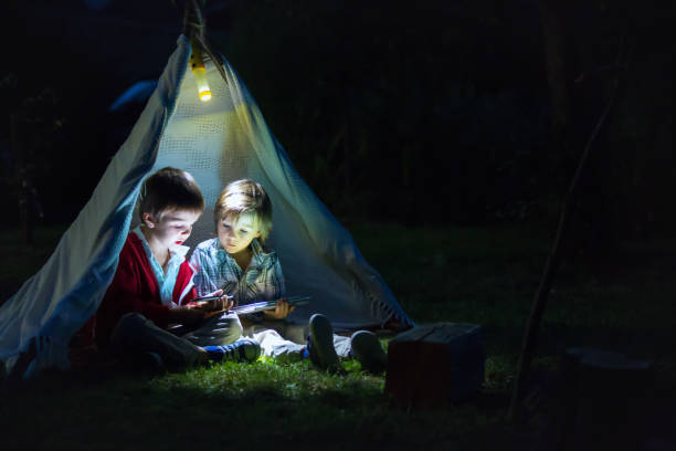 Cute little brothers, playing on tablet and telephone at night in campside, in the tent stock photo