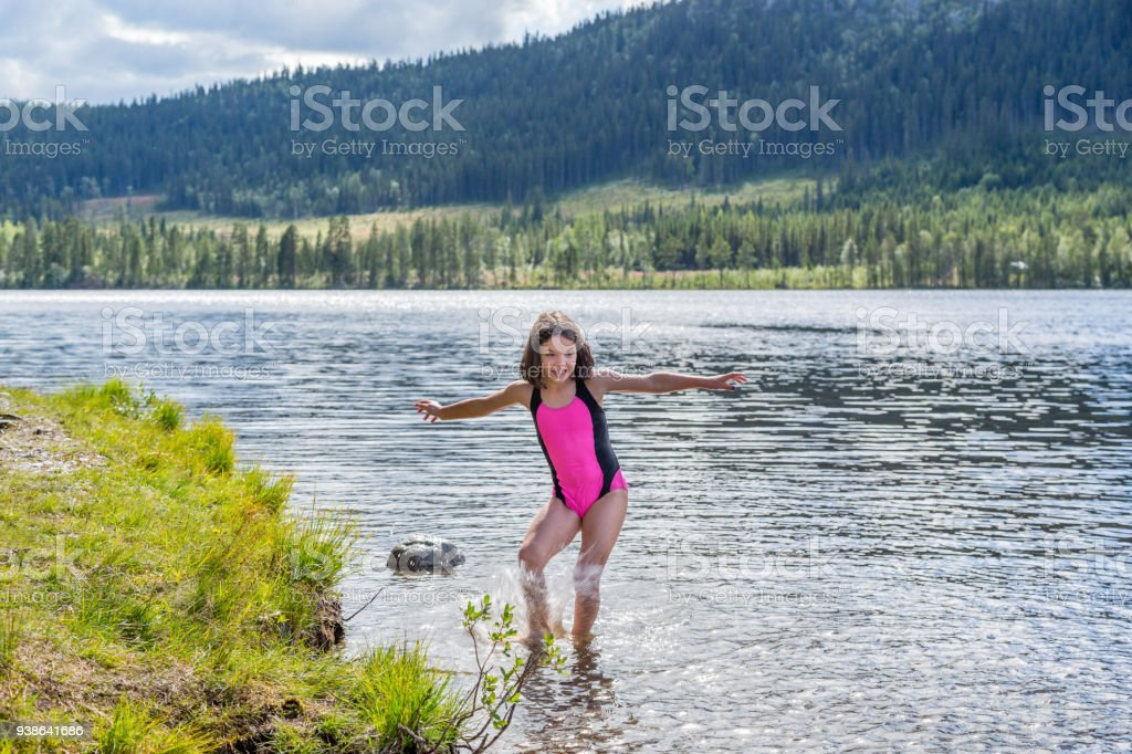 Cute little brown haired girl in swimsuit splashing water in a mountain lake. stock photo