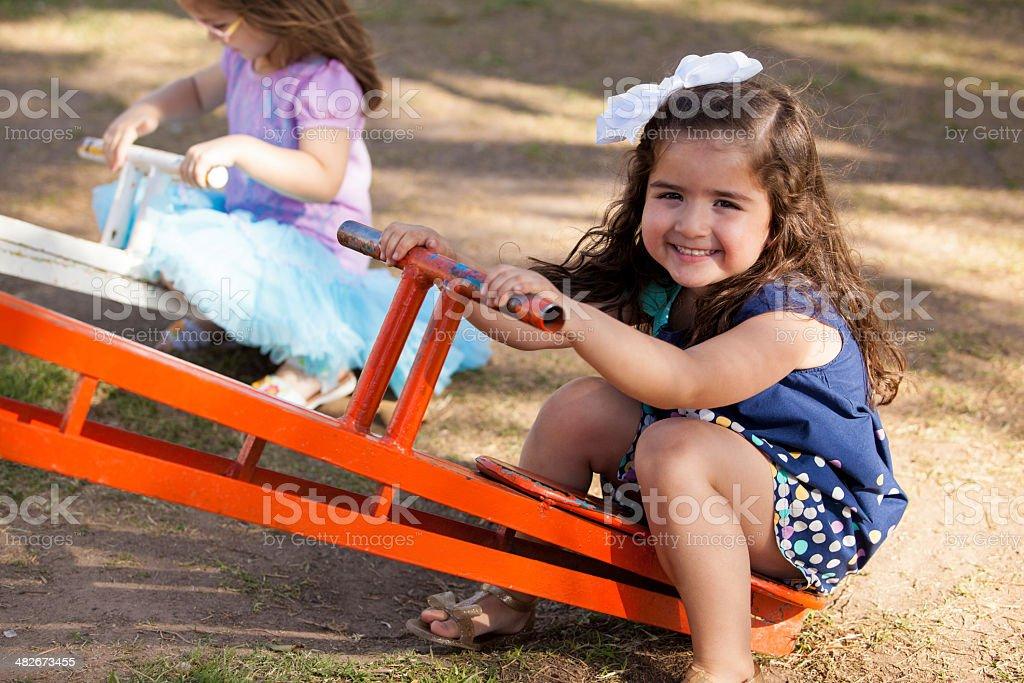 Cute little brunette in a seesaw stock photo