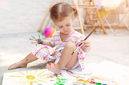 1042756824 istock photo Cute little caucasian Girl enjoying Painting at the backyard with paper, water colour and art brush. Selective focus 1033517180