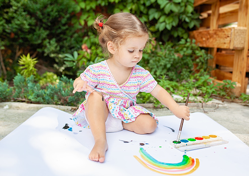 1042756824 istock photo Cute little caucasian Girl enjoying Painting at the backyard with paper, water colour and art brush. Selective focus 1033517184