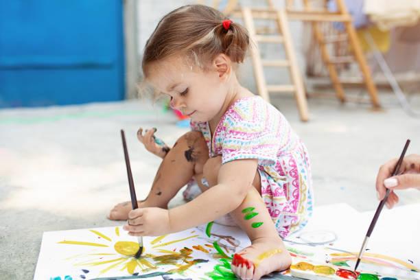 可愛的小高加索女孩喜歡在後院畫紙, 水顏色和藝術刷子。選擇性聚焦 - 畫畫 動態活動 個照片及圖片檔