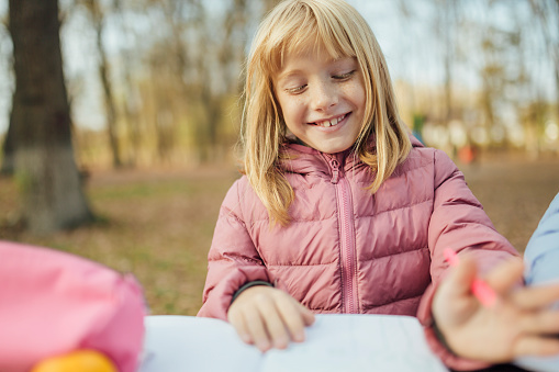 1042756824 istock photo Cute little caucasian twins sisters enjoying drawing at the backyard with paper 1217687571