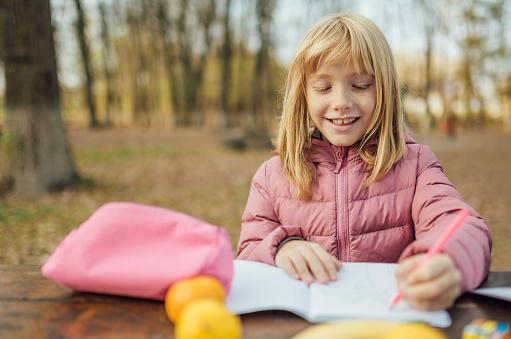 1042756824 istock photo Cute little caucasian twins sisters enjoying drawing at the backyard with paper 1217687572