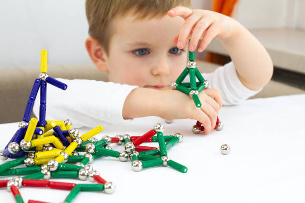 可愛的小男孩玩磁鐵玩具大腦發育, 精細的運動技能和創造力的概念 - 磁石 個照片及圖片檔
