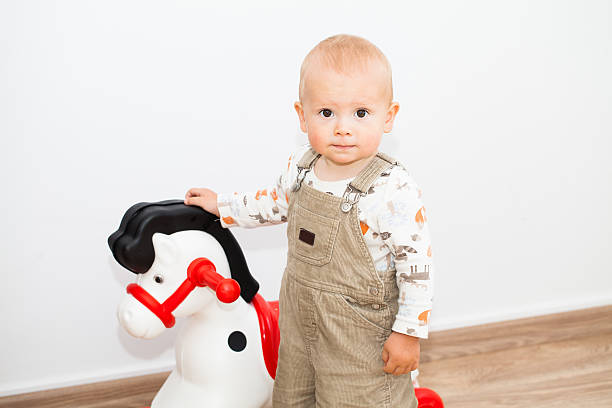 Cute little child boy with a horse toy, indoor stock photo
