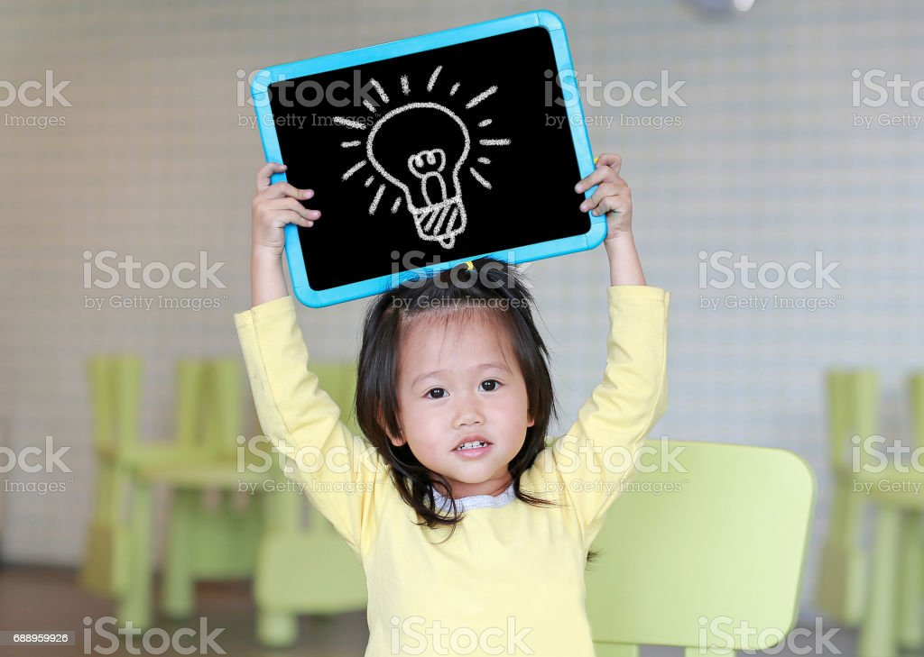 Cute little child girl holding blackboard showing bulbs image in kids room. Education concept. stock photo