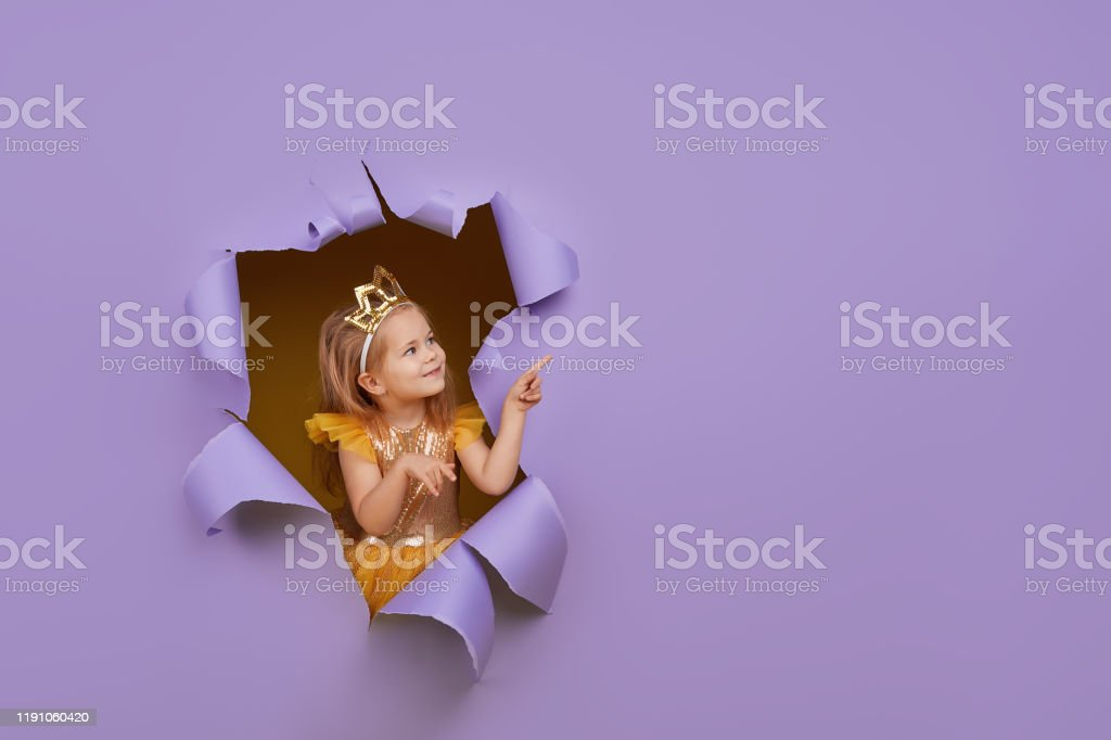 Cute little child girl in princess costume breaks through a colored...