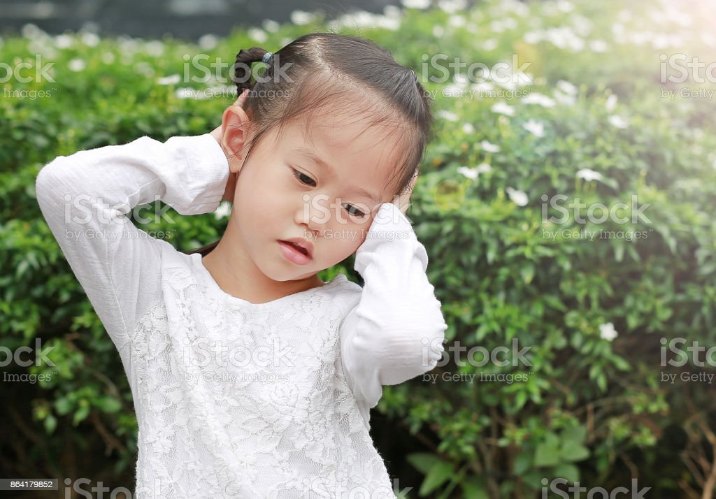 Cute little child girl shutting dawn her ears, holding her hands covers ears not to hear. stock photo