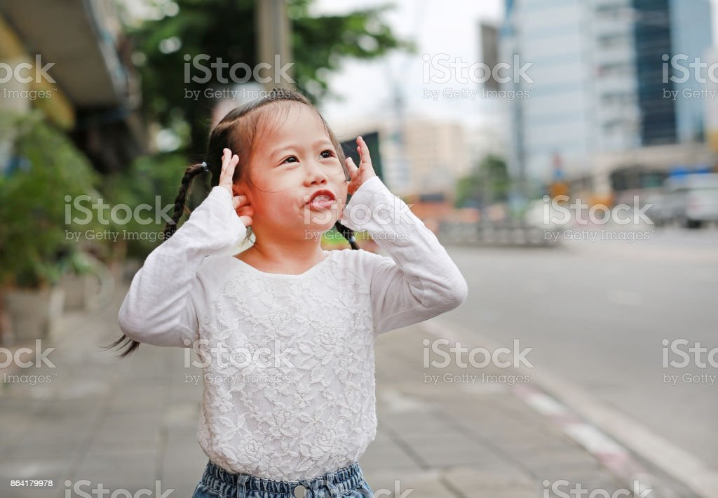 Cute little child girl shutting dawn her ears, holding her hands covers ears not to hear. royalty-free stock photo