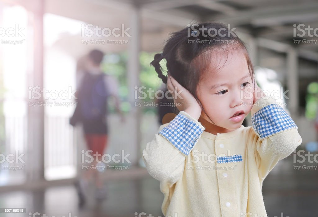 Cute little child girl shutting down her ears, holding her hands covers ears not to hear. stock photo