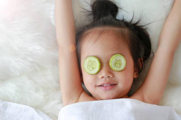 niedliche kleine kind mädchen mit einer scheibe gurke in ihren augen, konzept für die hautpflege. - make up torte stock-fotos und bilder