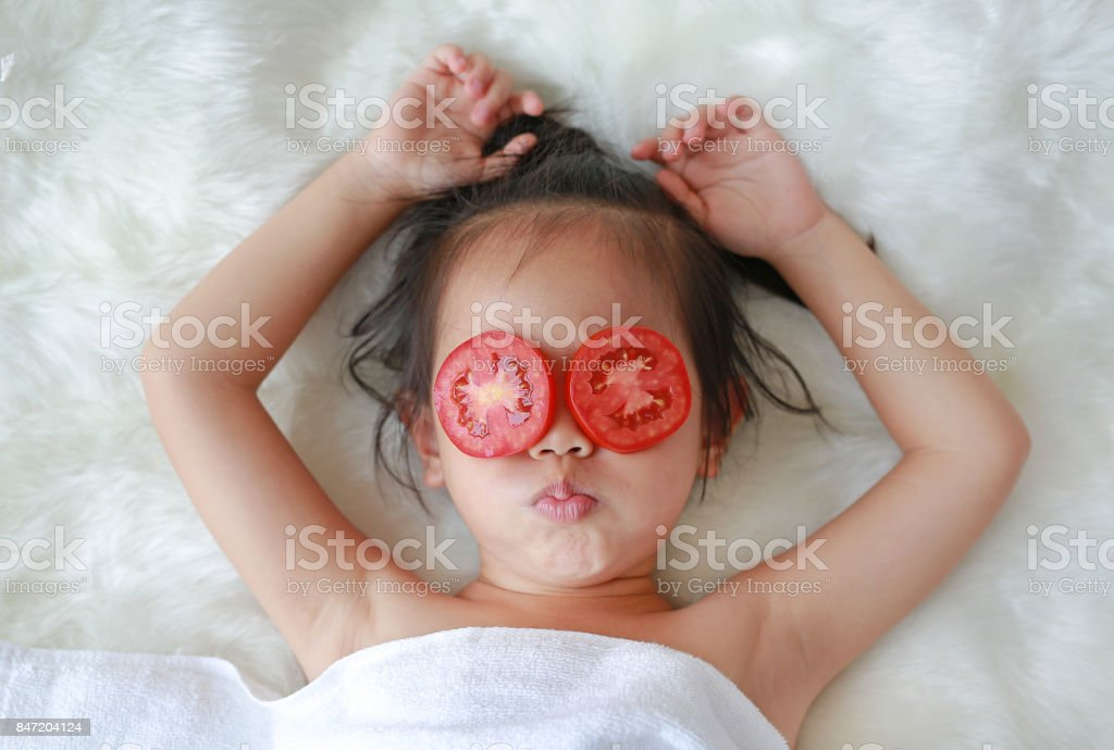 Cute little Child girl with a slice of tomato in her eye, concept for skin care. stock photo