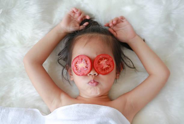 niedliche kleine kind mädchen mit einer scheibe tomate in ihren augen, konzept für die hautpflege. - make up torte stock-fotos und bilder